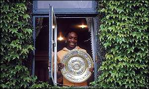 Venus Williams proudly displays her wares for winning her first of five Wimbledon women's singles title in 2000.